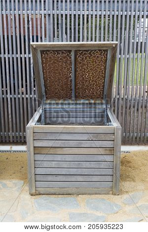 Single wooden compost bin with the lid open ready to accept composting scraps situated outside