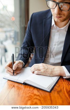 Busy financier making notes in notebook while planning working schedule