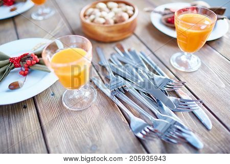 Silverware on wooden table with juice in glasses and plates with napkins near by