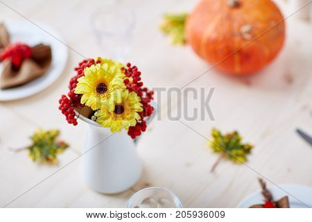 Yellow flowers and ripe ashberries in porcelain vase on festive table