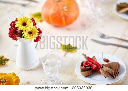 Flowers and ashberries in vase on wooden served festive table