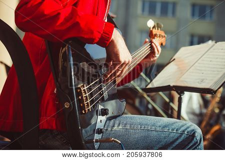 Novokuzneck Russia - 13.08.2017: the bass guitarist plays in the band on the street in the city of Novokuznetsk in Russia