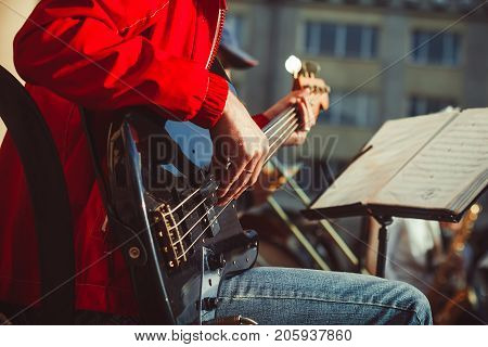 Novokuzneck Russia - 13.08.2017: the bass guitarist plays in the band on the street in the city of Novokuznetsk in Russia