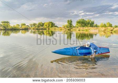 Male senior paddler rinsing his stand up paddleboard on a lake, late summer scenery in northern Colorado