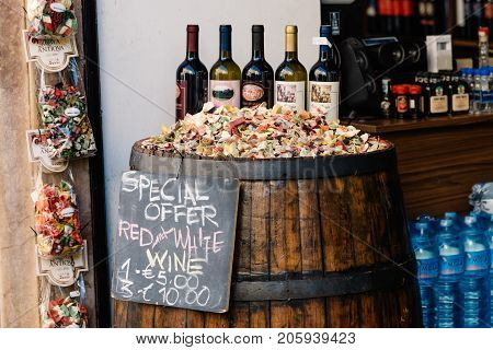 Rome, Italy - August 21, 2016: Storefront of grocery shop in Rome with offers for wine and other products