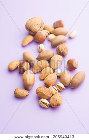Different types of nuts in the nutshell on purple background.