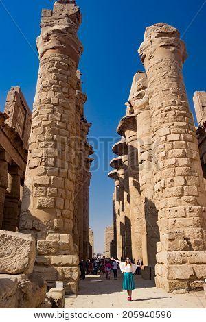 Girl near the statue in the temple of Karnak in Luxor, Egypt
