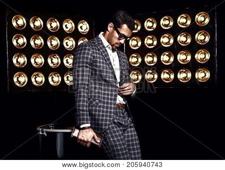 portrait of sexy handsome fashion male model man dressed in elegant suit studio lights background