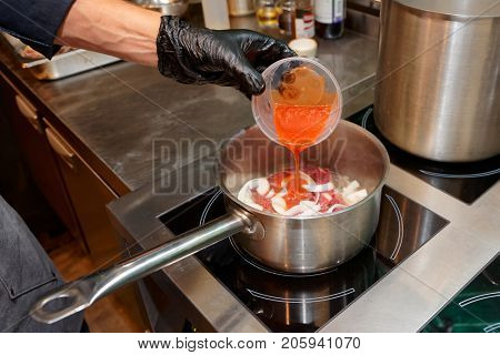 Gloved chef is adding strained tomatoes to a dish, professional kitchen