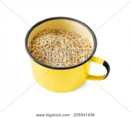 Enamel cup of long grain brown rice on white background