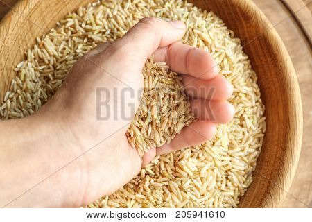 Female hand full of long grain brown rice
