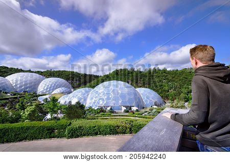 Eden Project, St Austell, Cornwall, United Kingdom - June 28, 2016: young man overlooking the geodesic biome domes of Eden Project and its gardens on a sunny summer´s day.