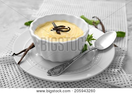 Vanilla pudding in ceramic bowl on grey table
