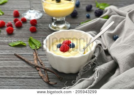 Composition with vanilla pudding, fresh mint and berries on wooden table