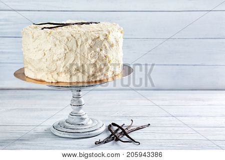 Vintage stand with delicious vanilla cake on wooden table