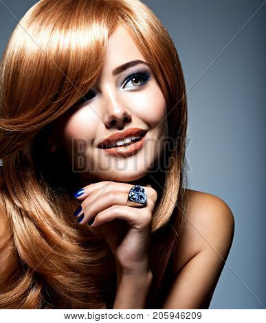 Face of a beautiful woman with sapphire jewelry ring on finger. Portrait  of young fashion model with blue eye makeup  poster