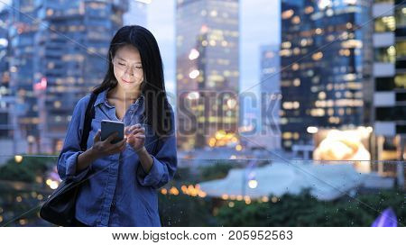 Asian woman text on mobile phone in city