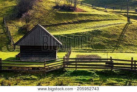 Woodshed Near The Fence On Grassy Hillside