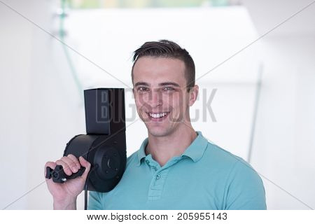 portrait of young hairstylist holding hairdryer looking at camera