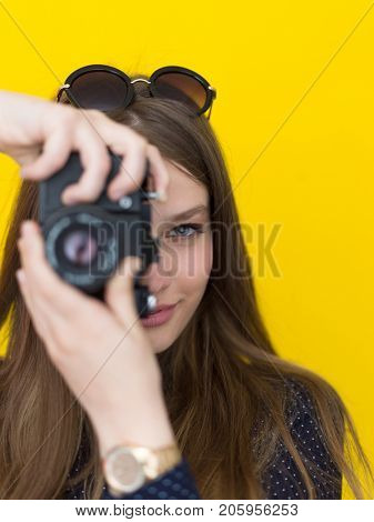 portrait of a smiling pretty girl taking photo on a retro camera isolated over yellow background