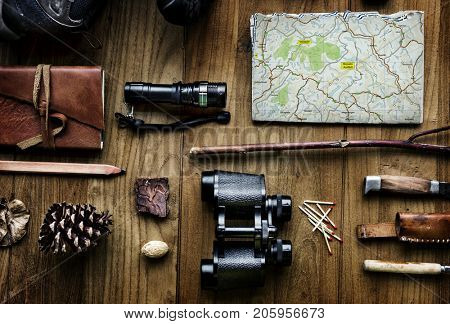 Aerial view of camping equipments and map on wooden table