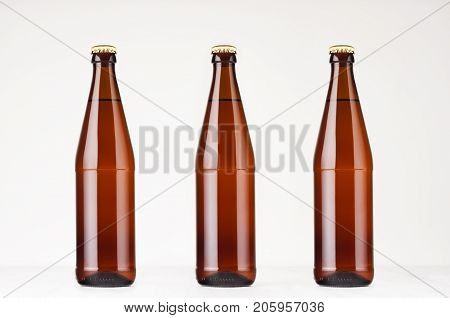 Set of three brown NRW beer bottles 500ml mock up. Template for advertising design branding identity on white wood table.