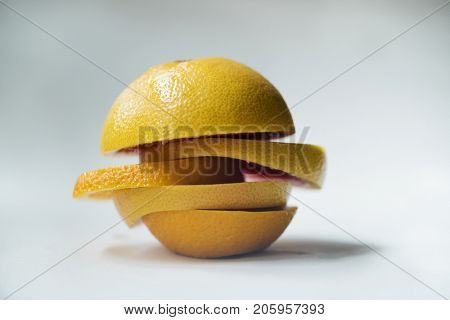 Closeup of oranges mixed with lemon pieces isolated on white