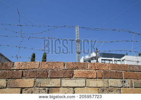 Barbed wire security fence added to a very high brick wall to prevent crime