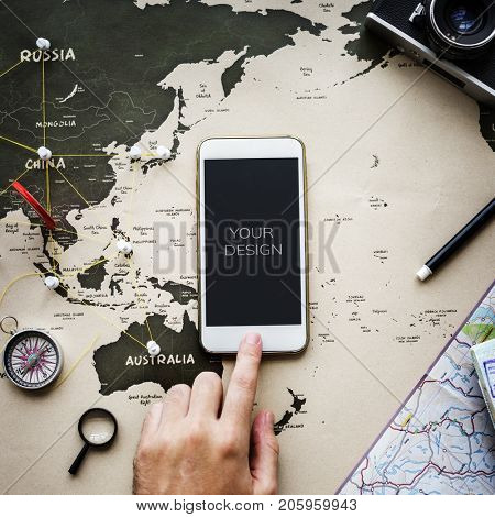 Closeup of hand with mobile phone over map background
