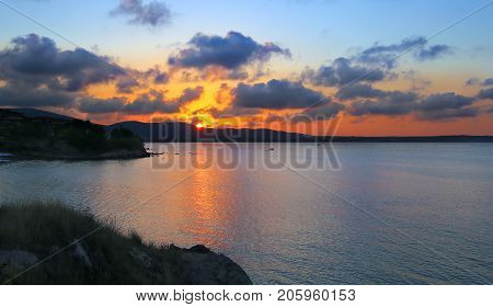 Sunset with clouds over the sea bay with hilly banks. Bulgaria Sozopol.
