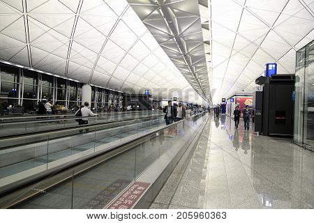 Hong Kong, China: April, 2017: Passengers traveling on the moving walkway at the International Airport in Hong Kong. It is located on the island of Chek Lap Kok.