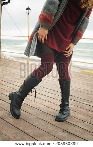Slim female legs dressed in knee high boots with shoelaces and knitted stockings, outdoor