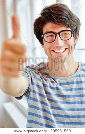 Young man holding thumbs up as a sign of success