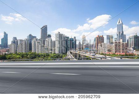 blur emtpy asphalt road and cityscape of shanghai in blue cloud sky