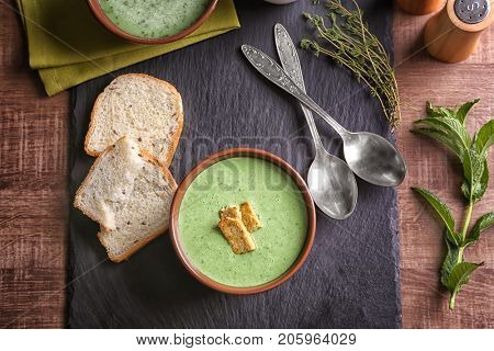 Puree from green peas in bowl with rusks on table