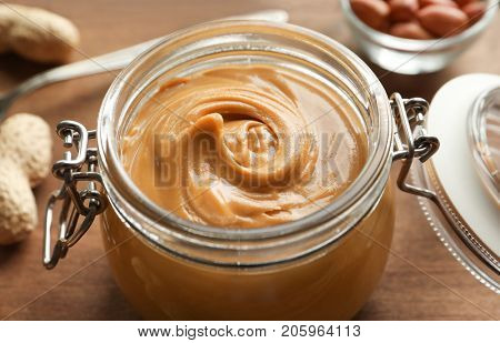 Glass jar with creamy peanut butter on kitchen table, closeup