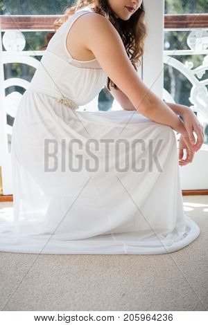 Low section of beautiful bride crouching by door at home