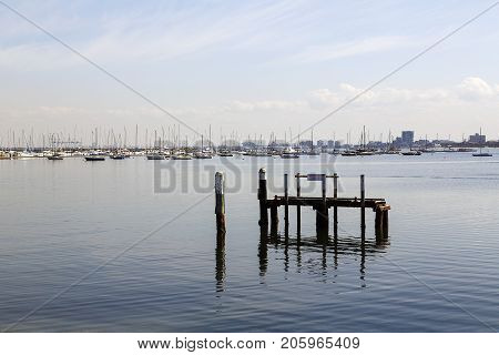 St Kilda, Victoria, Australia: April 04, 2017: St Kilda marina on a very calm blue sky day with yachts moored in the bay. This area is very popular with tourist and locals alike.