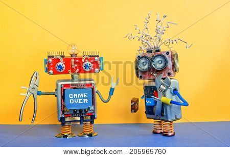 Industry 4.0 service repair maintenance concept. Creative design robotic toys, adjustable spanner silver pliers tools. Funny face robot, message Game over. Yellow blue background.