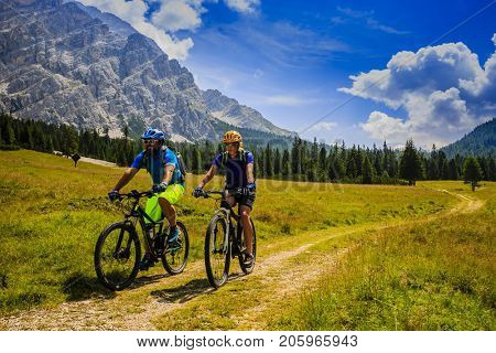 Tourists cycling in Cortina d'Ampezzo, stunning rocky mountains on the background. Man riding MTB enduro flow trail. South Tyrol province of Italy, Dolomites.
