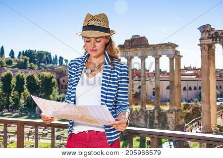 Roman Holiday. modern woman in the front of Roman Forum in Rome Italy looking at the map
