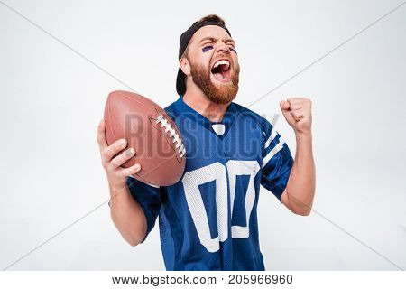 Image of excited screaming man fan in blue t-shirt standing isolated over white background. Eyes closed holding rugby ball.
