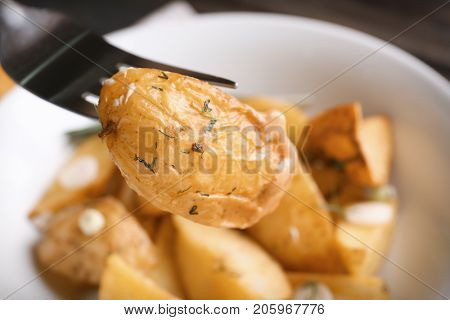 Fork with delicious baked potato wedge, close up