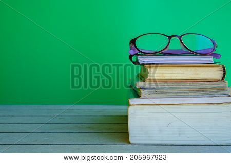 Stack of books and eye glasses on top on the wooden table and green background teacher's day concept.