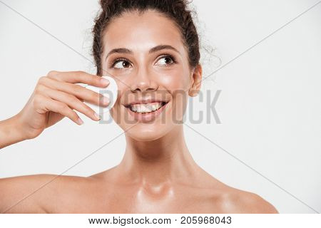 Beauty portrait of a smiling brunette woman with soft healthy skin removing make up with cotton pad isolated over white background