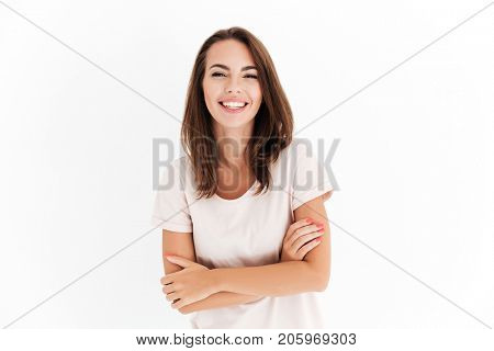 Laighing woman with crossed arms looking at the camera over white background