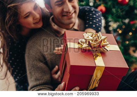 Young man and woman with a beautifully decorated gift box sitting near a Christmas tree. Happy couple celebrating Christmas together with gifts.