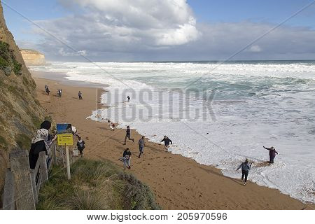 Melbourne, Australia: April 2, 2017: Tourists run from the incoming waves. They have walked down Gibson's Steps which is the only safe access to the beach.