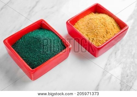 Spirulina and camu powders in red bowls on light background