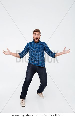 Full length portrait of a happy excited bearded man screaming and gesturing with hands isolated over white background